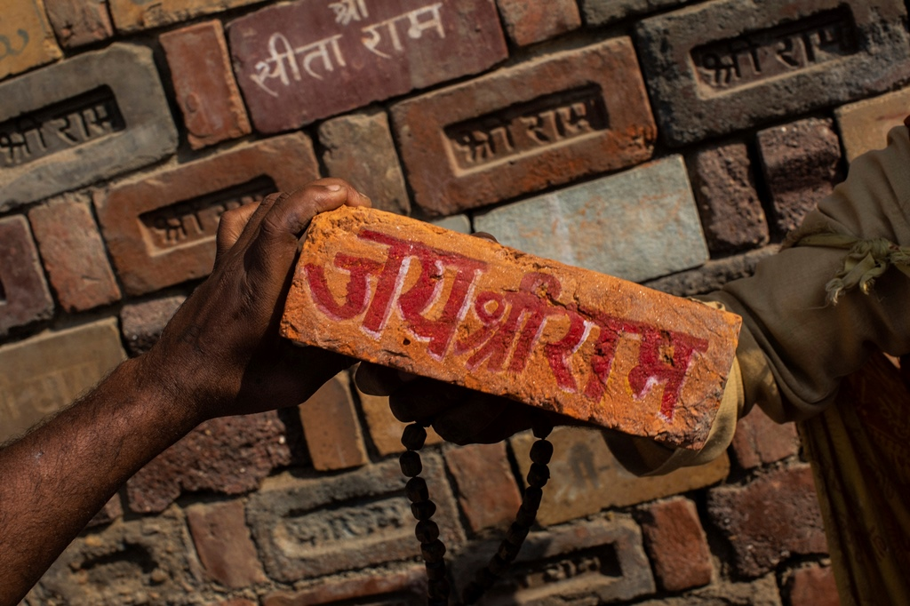 """Ayodhya: FILE - In this Sunday, Nov. 25, 2018 photo, a man holds a brick reading """"Jai Shree Ram"""" (Victory to Lord Ram) as bricks of the old Babri Mosque are piled up in Ayodhya, in the central Indian state of Uttar Pradesh. State-run broadcaster on Saturday, Nov. 9, 2019, said top court rules for disputed temple-mosque land for Hindus with alternate land to Muslims. Authorities increased security in Ayodhya, 550 kilometers (350 miles) east of New Delhi, and deployed more than 5,000 paramilitary forces to prevent any attacks by Hindu activists on Muslims, who comprise 6% of the town's more than 55,500 people. AP/PTI(AP11_9_2019_000038B)"""