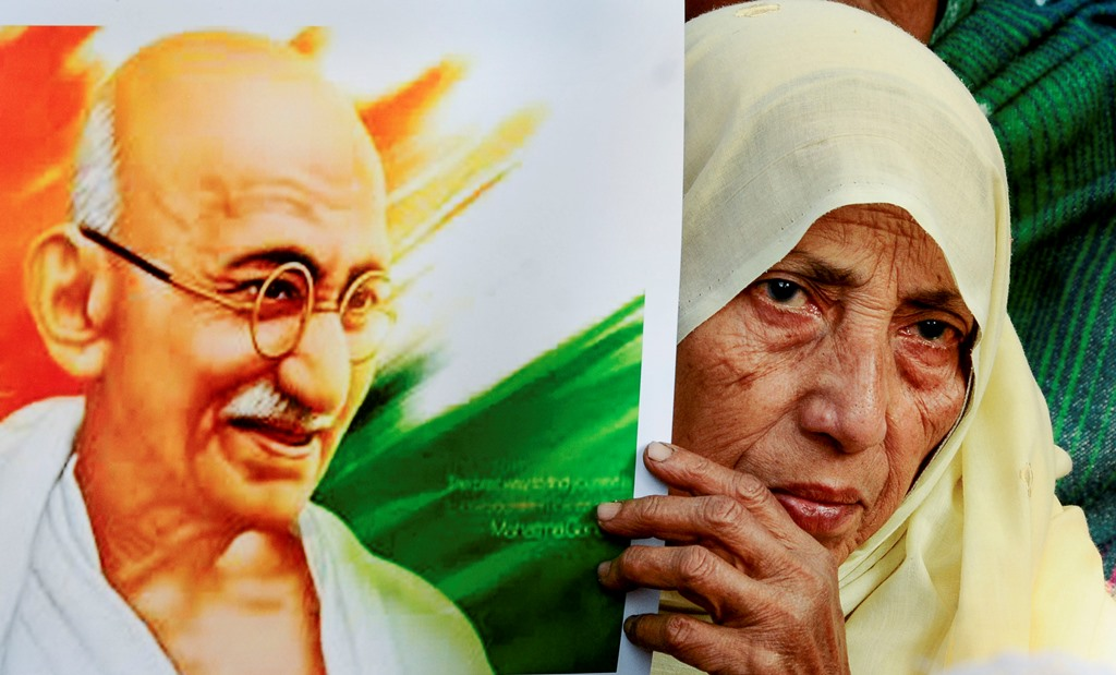 New Delihi: An elderly protestor holds a picture of Mahatma Gandhi during a protest against the new Citizenship Act, outside the Jamia Millia Islamia University in New Delhi, Friday, Jan. 3, 2020. (PTI Photo) (PTI1 3 2020 000190B)