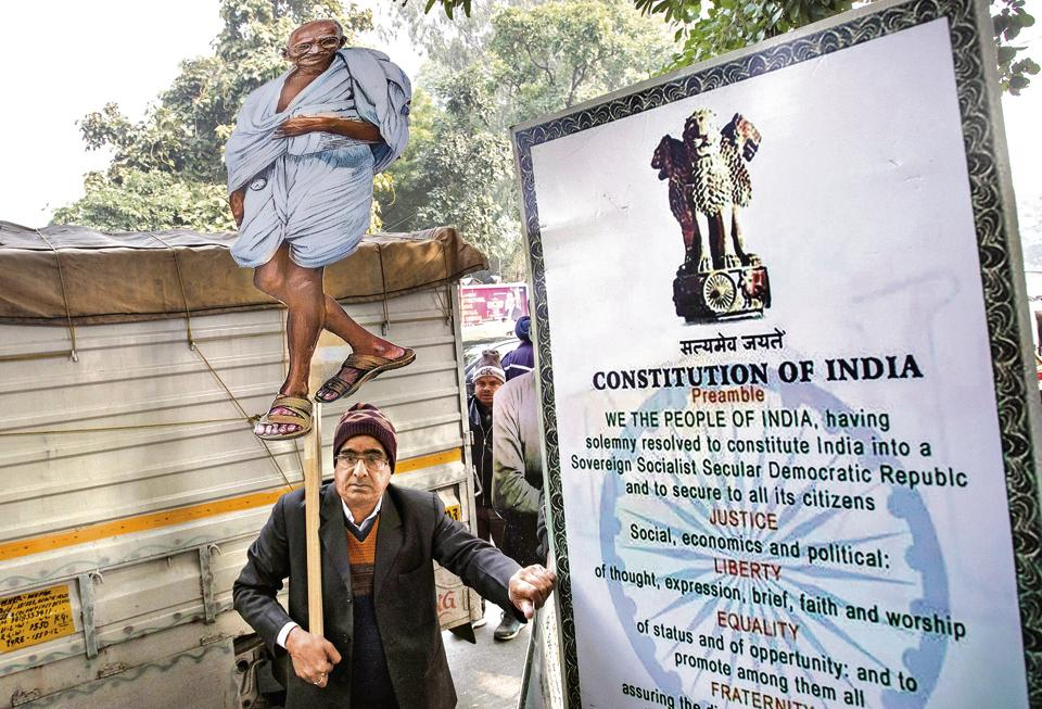 The massive protests against the CAA have brought the Constitution into the public discourse. A demonstrator stands next to a hoarding of the Preamble to the Constitution in Delhi. (REUTERS)