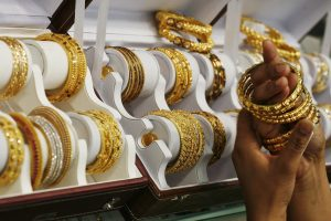 A customer tries gold bangles inside a jewellery showroom at Noida in the northern Indian state of Uttar Pradesh in this April 21, 2011 file photo. India's passion for gold is putting such a strain on state finances that the government may slap higher import taxes on the precious metal, but demand buoyed by heady inflation and meagre savings will blunt the impact of any rise in duties as reported January 16, 2013. REUTERS/Parivartan Sharma)