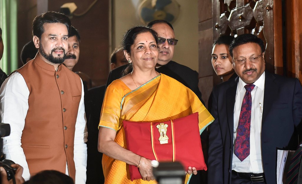 New Delhi: Union Finance Minister Nirmala Sitharaman, flanked by her deputy Anurag Thakur (L) and a team of officials, shows a folder containing the Union Budget documents, at Parliament in New Delhi, Saturday, Feb. 1, 2020. (PTI Photo/Manvender Vashist) (PTI2_1_2020_000027B)