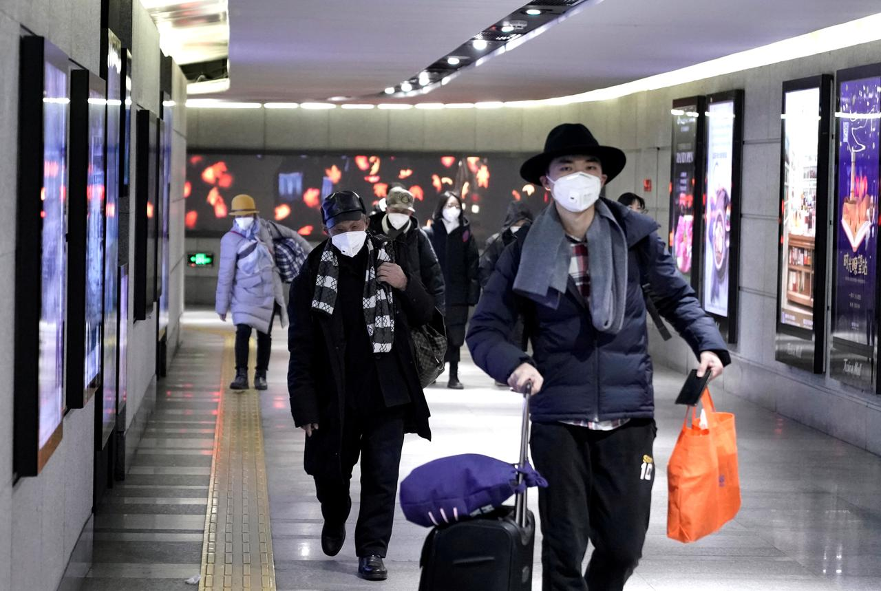 People wearing masks walk through an underground passage to the subway in Beijing, China January 21, 2020. REUTERS/Jason Lee