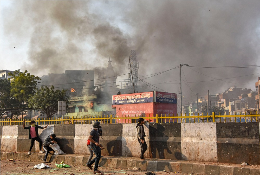New Delhi: Protestors throw brick-bats during clashes between a group of anti-CAA protestors and supporters of the new citizenship act, at Chand Bagh in Bhajanpura, in north-east Delhi, Monday, Feb. 24, 2020. (PTI Photo)  (PTI2_24_2020_000248B) *** Local Caption ***