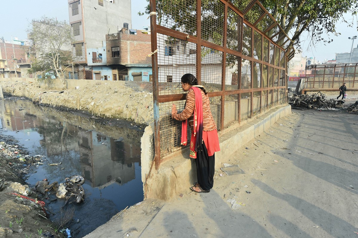 **EDS: GRAPHIC CONTENT**New Delhi: A passer-by looks at an abandoned body lying in a nullah at Brahampuri area following communal violence over the amended citizenship law, in northeast Delhi, Thursday, Feb. 27, 2020. (PTI Photo/Arun Sharma)(PTI2_27_2020_000050B)