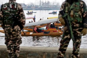 Foreign diplomats are seen in boats as Indian security force personnel stand guard on the banks of Dal Lake in Srinagar February 12, 2020. REUTERS/Danish Ismail