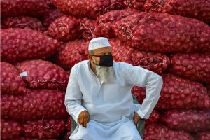 Ghaziabad: A vendor, wearing mask, sits near sacks of onions at the Sahibabad fruits and vegetables market in Ghaziabad, Tuesday, March 24, 2020. Ghaziabad is one of the 17 districts of Uttar Pradesh which has been put under lockdown at least until March 25, to contain the coronavirus disease (Covid-19). (PTI Photo/Ravi Choudhary)(PTI24-03-2020 000065B)