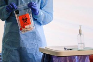 A healthcare worker holding a completed test with patient samples at a drive-through testing site for coronavirus, flu and RSV in Seattle, Washington state [Lindsey Wasson/Reuters]