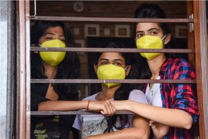 Jodhpur: Women, wearing masks, look out from a window of their house during the complete lockdown imposed in the wake of the novel coronavirus pandemic, in Jodhpur, Wednesday, March 25, 2020. (PTI Photo) (PTI25-03-2020 000208B)