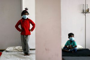 Children of migrant workers wear protective masks inside a sports complex turned into a shelter, during a 21-day nationwide lockdown to slow the spread of the coronavirus disease (COVID-19), in New Delhi, India, April 4, 2020. REUTERS/Adnan Abidi