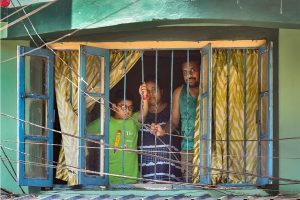 Kolkata: A family looks from the window of a house during the nationwide lockdown imposed to contain the coronavirus pandemic, in Kolkata, Tuesday, March 31, 2020. (PTI Photo/Swapan Mahapatra) (PTI31-03-2020 000112B
