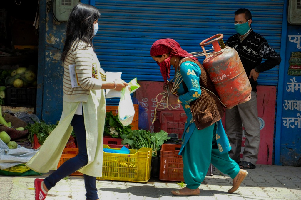 Kullu: A woman carries a LPG cylinder on her back as another woman walks past her, during the nationwide lockdown to curb the spread of coronavirus, in Kullu, Monday, April 27, 2020. (PTI Photo)(PTI27-04-2020_000135B)