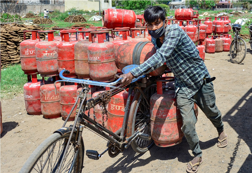 New Delhi: A worker carries LPG gas cylinders on his bicycle for delivery during the nationwide lockdown imposed in the wake of coronavirus pandemic, in New Delhi, Wednesday, April 8, 2020. (PTI Photo/Kamal Kishore)(PTI08-04-2020 000261B)