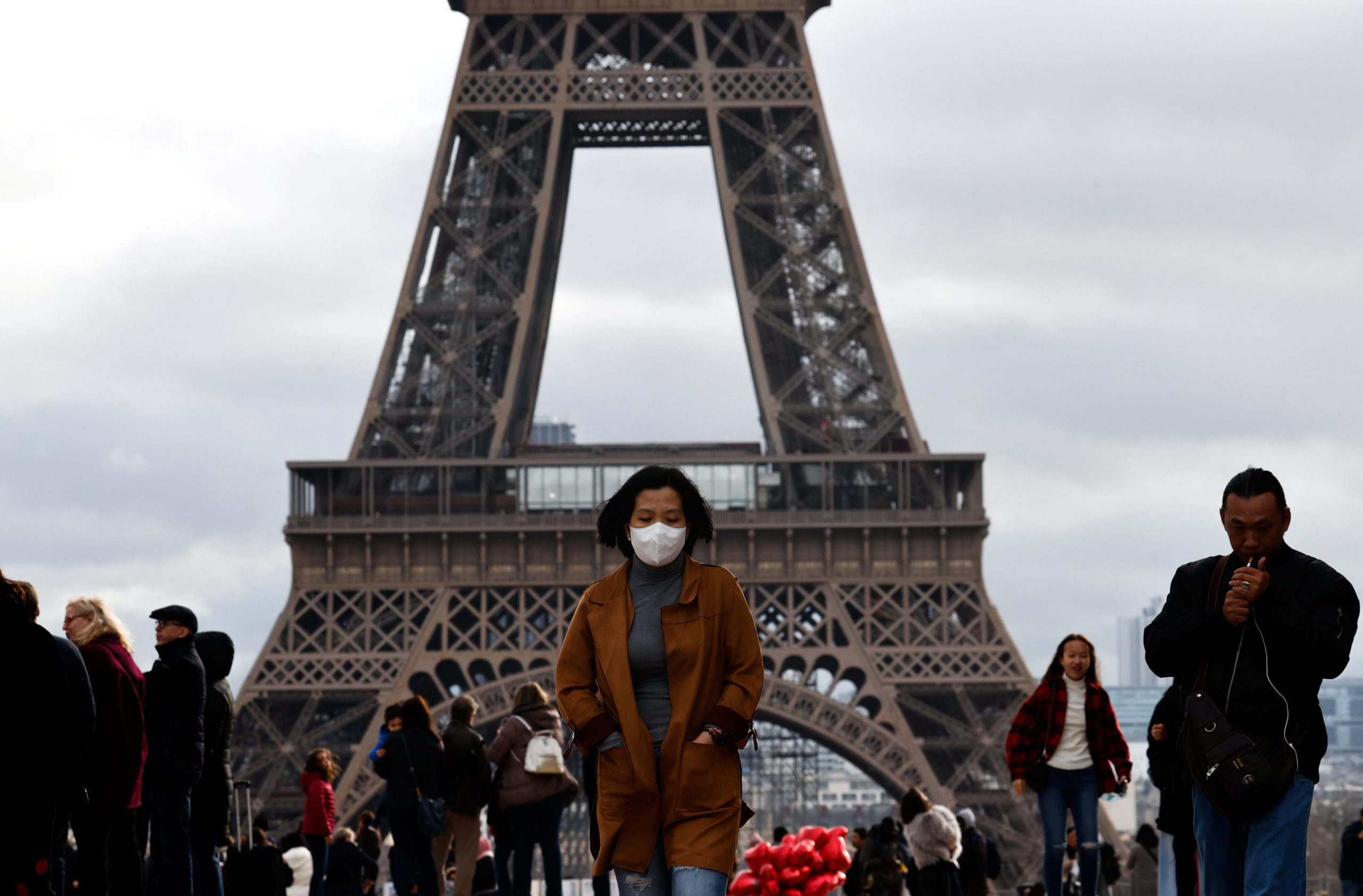 A woman wears a protective mask in light of the coronavirus outbreak in China as she walks at the Trocadero esplanade in front of the Eiffel Tower in Paris, France. (Photo March 2020/REUTERS/Gonzalo Fuentes)