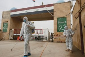 Workers in protective suits spray disinfectants near the gate of Shalamcha Border Crossing, after Iraq shut a border crossing to travellers between Iraq and Iran, Iraq March 8, 2020. REUTERS/Essam al-Sudani