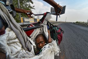 New Delhi: A physically challenged girl sits on a makeshift seat of a bicycle as she travels with her family to UP, during the ongoing COVID-19 nationwide lockdown, in New Delhi, Sunday, May 17, 2020. (PTI Photo/Arun Sharma)(PTI17-05-2020_000179B)