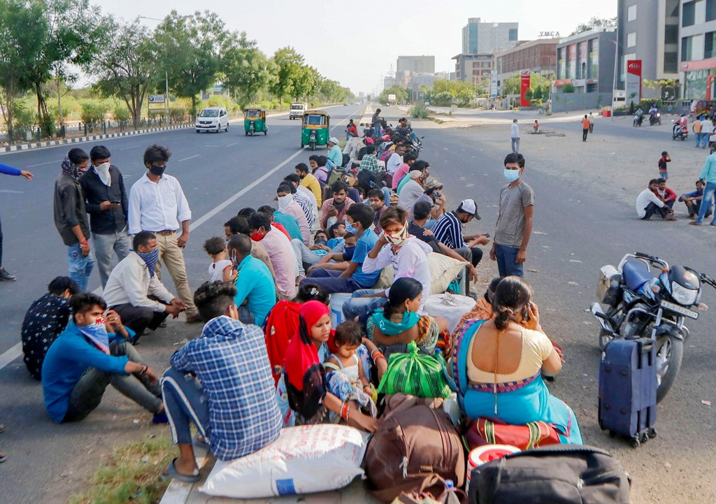 Ahmedabad: Migrants wait for a transport to reach the railway station and board a special train to their native places in Uttar Pradesh, amid the ongoing COVID-19 lockdown, in Ahmedabad, Thursday, May 14, 2020. (PTI Photo) (PTI14-05-2020_000070B)