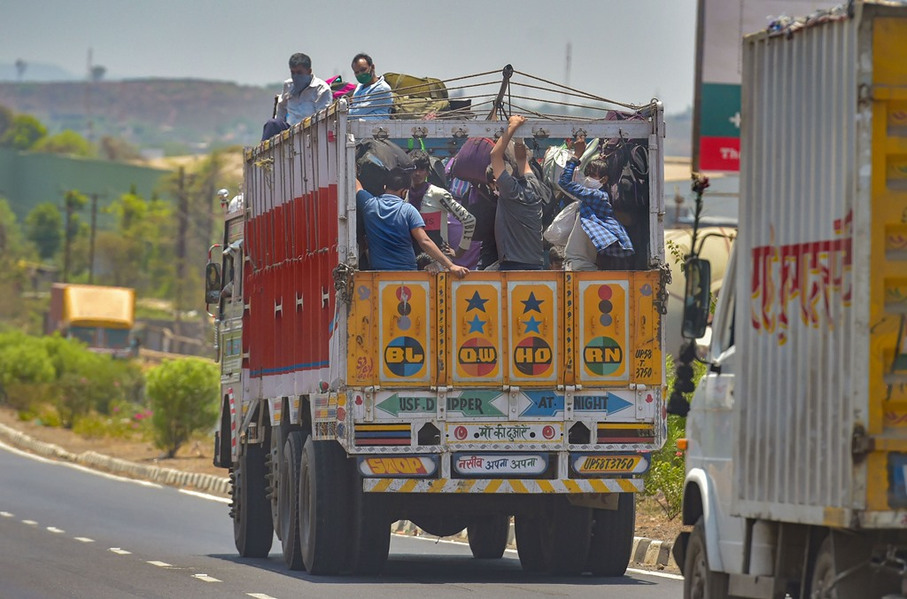 Thane : Migrants from various northern states travel in a truck at the Mumbai-Nashik highway to reach their native places, during the ongoing COVID-19 nationwide lockdown, in Thane, Monday, May 11, 2020. (PTI Photo/Mitesh Bhuvad)(PTI11-05-2020_000128B)
