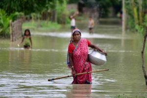 Nagaon: A woman wades through a flooded area at a village, in Nagaon district, Saturday, June 27, 2020. (PTI Photo)(PTI27-06-2020 000076B)