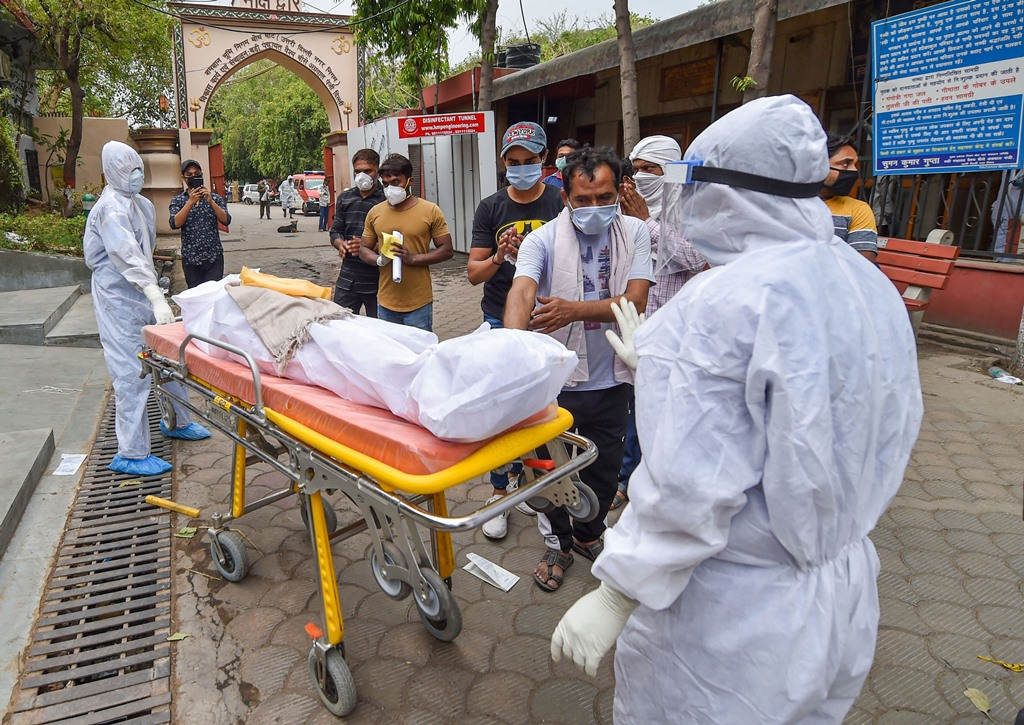 New Delhi: Medics in protective suits carry the body of COVID-19 patient for cremation at Nigam Bodh Ghat, amid ongoing nationwide lockdown, in New Delhi, Friday, May 29, 2020. (PTI Photo/Manvender Vashist)(PTI29-05-2020_000158B)