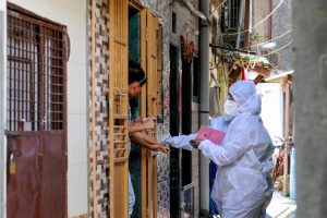 Mumbai: A health worker marks the hands of residents with home quarantine stamp, at Bhaji Galli Road no. 3 of Andheri East in Mumbai, Saturday, June 27, 2020. (PTI Photo)