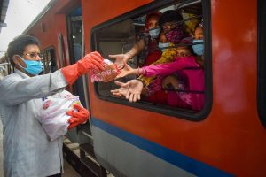 Prayagraj: A railway staff member distributes food packets among migrants sitting in Shramik Special train to reach their native places, during ongoing COVID-19 lockdown, at Prayagraj Railway Station, Sunday, May 31, 2020. (PTI Photo)(PTI31-05-2020_000074B)
