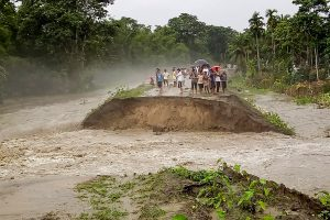 Barpeta: People stand near an embankment after it was washed away by floodwater during heavy rainfall, at Pathsala in Barpeta district, Sunday, July 12, 2020. (PTI Photo)(PTI12-07-2020_000266B)