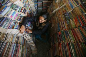 Ishwori Sapkota arranges books at her book store in Kathmandu December 18, 2011. She has been selling and buying second hand books for the past eighteen years. REUTERS/Navesh Chitrakar