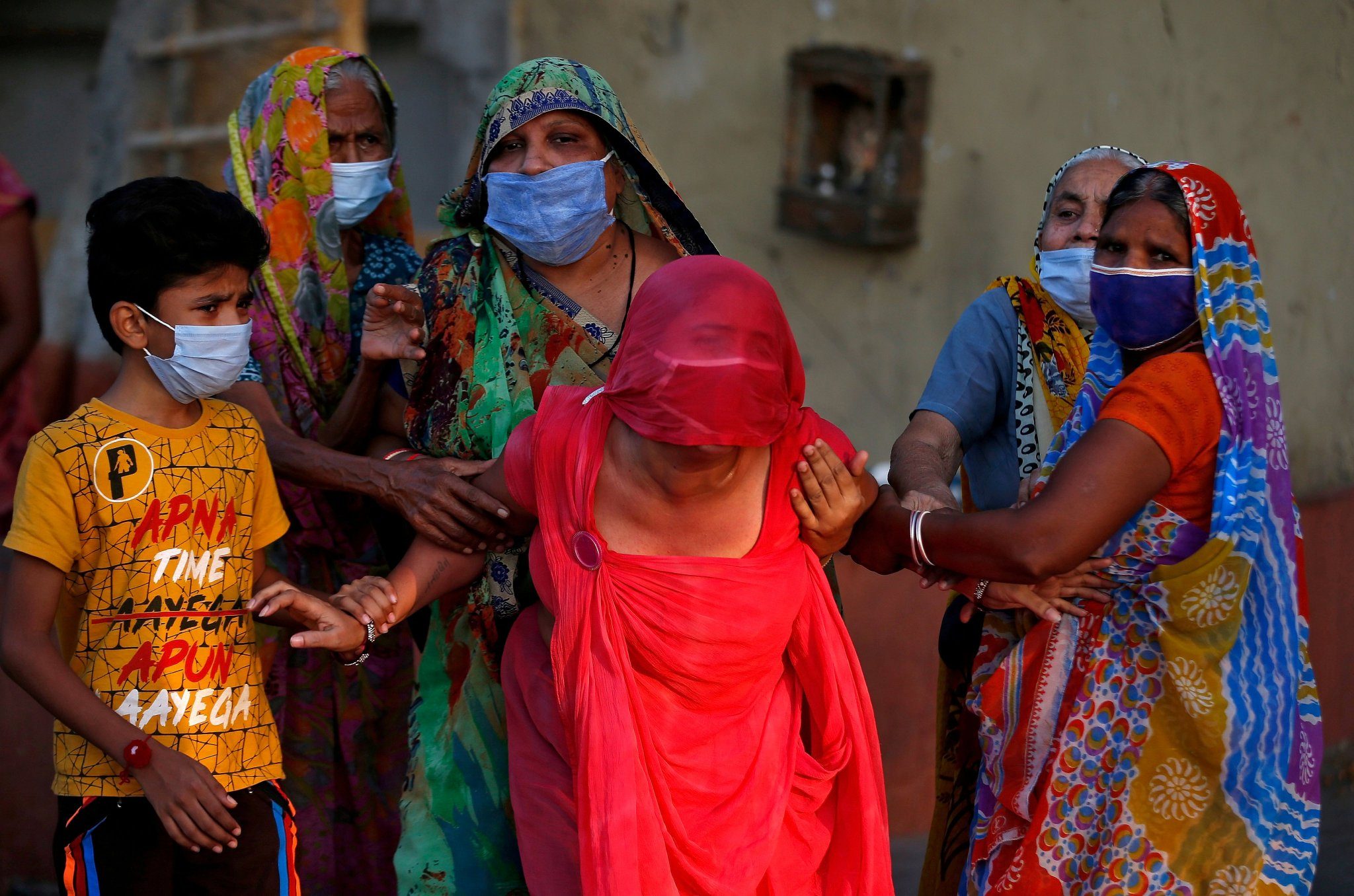 Relatives of a girl who died due to the coronavirus disease mourn outside a crematorium in Ahmedabad, India. May 2020. REUTERS/Amit Dave