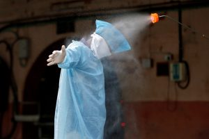 A municipal worker is sanitised after he cremated the body of a man, who died due to coronavirus disease, at a crematorium in Ahmedabad. Reuters