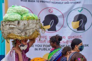 Bengaluru: A vendor carries bundles of flowers to sell during the festive season, in Bengaluru, Monday, Oct. 19, 2020. (PTI Photo/Shailendra Bhojak)(PTI19-10-2020 000209B)