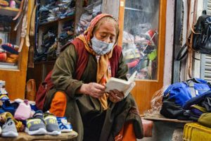 Leh: An elderly woman reads a book outside her shop at the main market, in Leh, Saturday, June 27, 2020. (PTI)