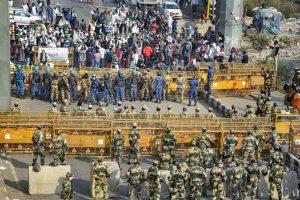 New Delhi: Police stand guard as Bharatiya Kisan Union (BKU) members protest at Ghazipur border during their Delhi Chalo march against the new farm laws, in New Delhi, Monday, Nov. 30, 2020. (PTI Photo/Ravi Choudhary)(PTI30-11-2020 000111B)