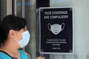 A woman wears a protective mask next to a sign urging to wear face coverings at a store, as the spread of the coronavirus disease (COVID-19) continues, in London, Britain July 24, 2020. REUTERS/Simon Dawson