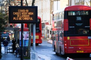 London buses pass a public health information message as new restrictions come into force Photograph: Toby Melville/Reuters