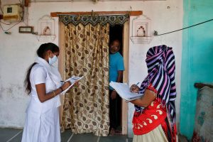 Health workers collect personal data from a man as they prepare a list during a door-to-door survey for the first shot of COVID-19 vaccine for people above 50 years of age and those with comorbidities, in a village on the outskirts of Ahmedabad, India, December 14, 2020. REUTERS/Amit Dave##########x##########