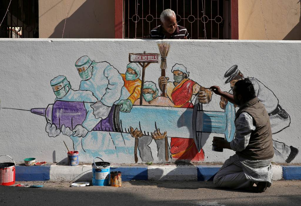 A man applies finishing touches to graffiti representing a vaccine, amidst the spread of coronavirus disease (COVID-19) in Kolkata, India, January 2, 2021. REUTERS/Rupak De Chowdhuri