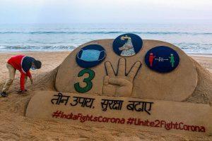Sand artist Sudarsan Pattnaik creates a sand sculpture on the novel coronavirus with an awareness message at Puri beach of Odisha. PTI Photo