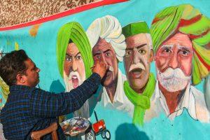 सिंघु बॉर्डर पर किसानों की पेंटिंग बनाता कलाकार. (फोटो: पीटीआई)