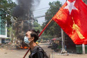 यंगून में तख्तापलट के खिलाफ नेशनल लीग फॉर डेमोक्रेसी का झंडा लेकर प्रदर्शन करते हुए एक प्रदर्शनकारी. (फोटो: रॉयटर्स)