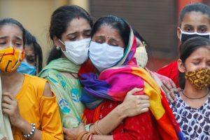 कोरोना संक्रमित व्यक्ति की मौत के बाद दिल्ली के एक शवदाह गृह में शोक संतप्त परिजन. (फोटो: रॉयटर्स)