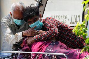 दिल्ली के लोकनायक जयप्रकाश नारायण अस्पताल के बाहर कोविड-19 से एक महिला की मौत के बाद शोक संतप्त परिवार. (फोटोः राॅयटर्स)