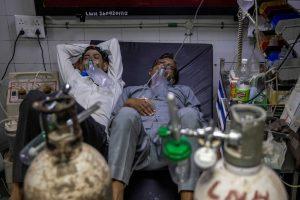 दिल्ली के जयप्रकाश नारायण अस्पताल के एक वार्ड में एक ही बेड पर लेटे कोरोना संक्रमित दो लोग. (फोटो: रॉयटर्स)