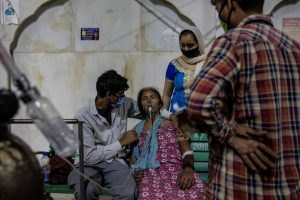 उत्तर प्रदेश के गाजियाबाद शहर के एक गुरुद्वारा में कोविड-19 महामारी के बीच सांस में तकलीफ बाद ऑक्सीजन के सहारे एक महिला. (फोटो: रॉयटर्स)