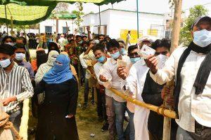 यूपी के रामपुर में पंचायत चुनाव के दौरान एक केंद्र पर मतदाता. (फोटो: पीटीआई)