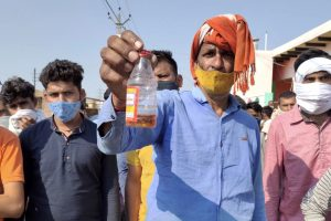 अलीगढ़ जिले एक अनुबंधित दुकान से खरीदी गई जहरीली शराब की बोतल दिखाता एक ग्रामीण. (फोटो: पीटीआई)