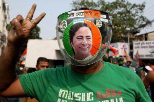 पश्चिम बंगाल चुनाव के परिणामों में तृणमूल कांग्रेस के जीत की ओर बढ़ने की खबर के बीच कोलकाता में पार्टी का एक कार्यकर्ता कोरोना फेसशील्ड पहनकर विक्ट्री साइन दिखाते हुए. (फोटो: रॉयटर्स)