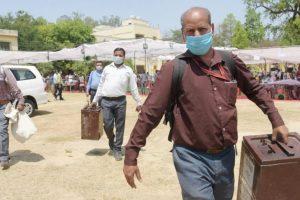 पंचायत चुनाव के दौरान लखनऊ के एक केंद्र पर बैलेट ले जाते कर्मचारी. (फोटो: पीटीआई)