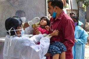 हैदराबाद के मुशराबाद क्षेत्र के एक स्वास्थ्य केंद्र में एक बच्ची की कोरोना जांच के लिए सैंपल कलेक्ट करते स्वास्थ्यकर्मी. (फोटो: पीटीआई)